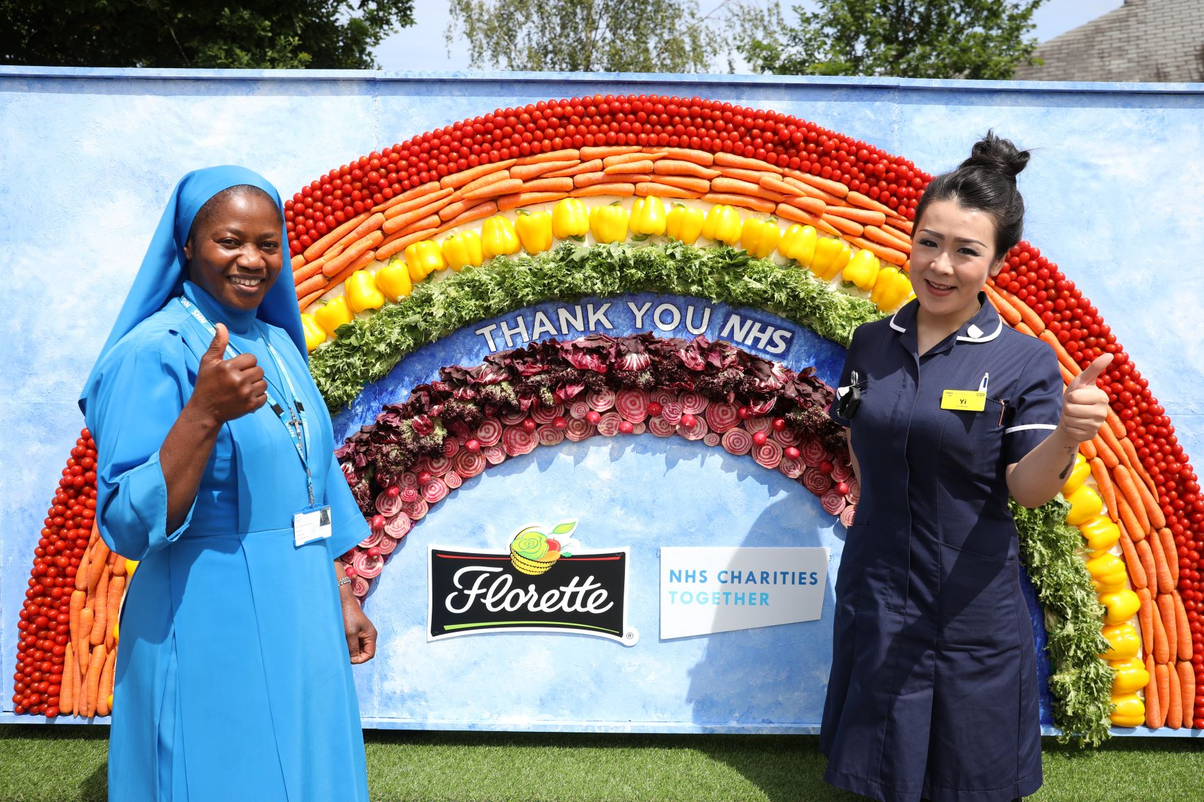 NHS frontline staff give a thumbs up in front of a rainbow made of salad to mark NHS Frontline Day resized